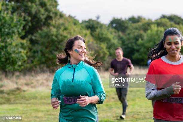 muddy women running cross country for charity event - charity benefit stock pictures, royalty-free photos & images
