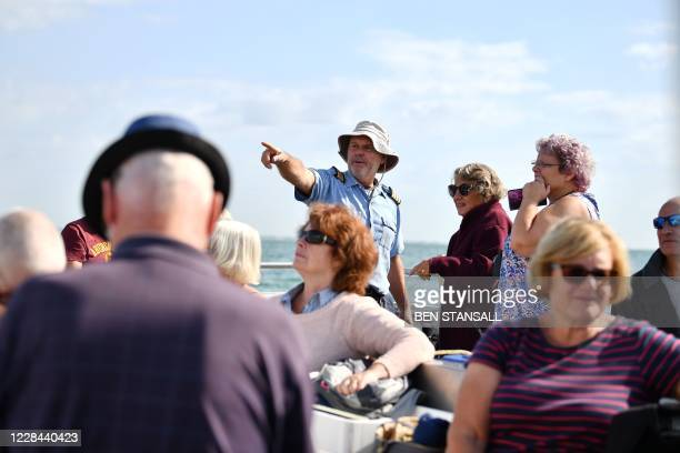 Mudeford Ferry's cruise ship tour captain Paul Derham speaks with passengers off the Dorset coast in southern England on September 10, 2020. -...