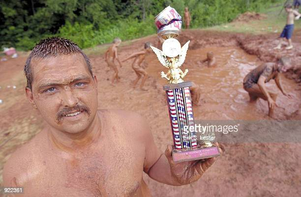 Mudpit Belly Flop champion Ron Johnson shows off his trophy during the Seventh Annual Summer Redneck Games on July 6, 2002 in East Dublin, Georgia....