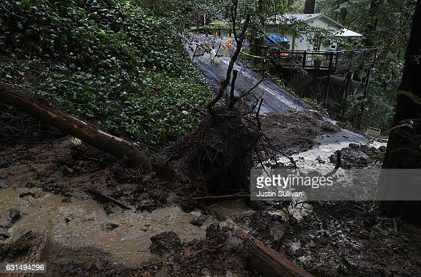 A mudslide carries debris down a hill next to a home on January 11 2017 in Guerneville California A new round of storms are bringing heavy rains and...