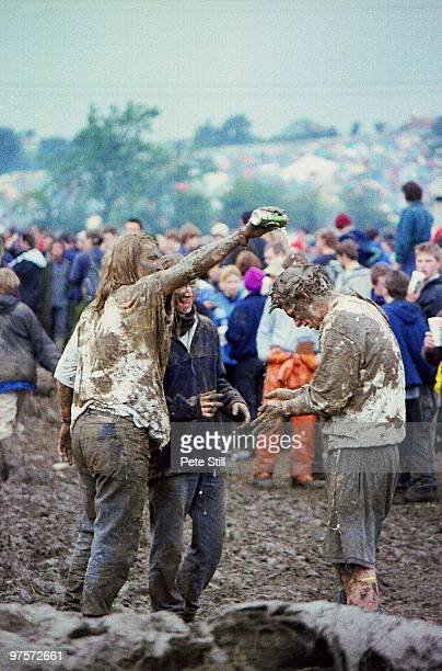 Mudspattered rock festival goers amuse themselves between band performances at the Glastonbury Festival on June 28th 1997 in Glastonbury England