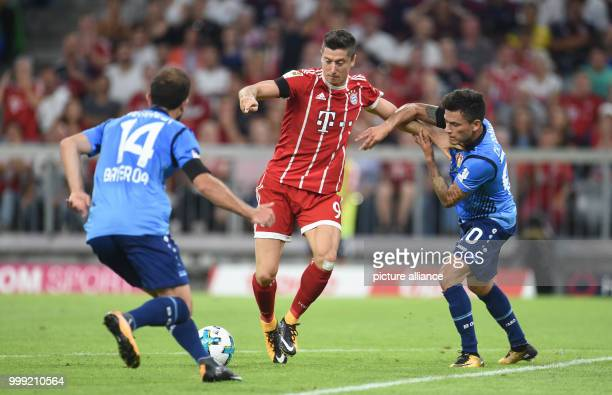 Muenchen's Robert Lewandowski and Leverkusen's Admir Mehmedi and Charles Mariano Aranguiz vie for the ball during the German Bundesliga soccer match...