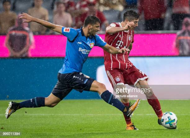 Muenchen's Robert Lewandowski and Leverkusen's Aleksandar Dragovic vie for the ball during the German Bundesliga soccer match between Bayern Muenchen...