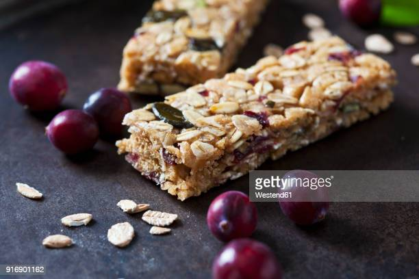 Muesli bars with cranberries and oat flakes on dark background
