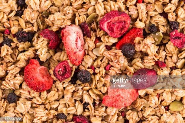 muesli cereals close up background with  raisins, oat and wheat flakes, fruits, strawberry, cranberry, cherry pieces - céréale photos et images de collection