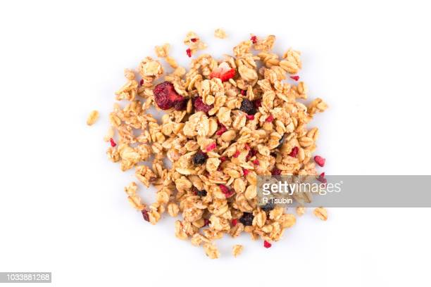 Muesli cereals close up with  raisins, oat and wheat flakes, fruits, strawberry, cranberry, cherry pieces. Isolated on white