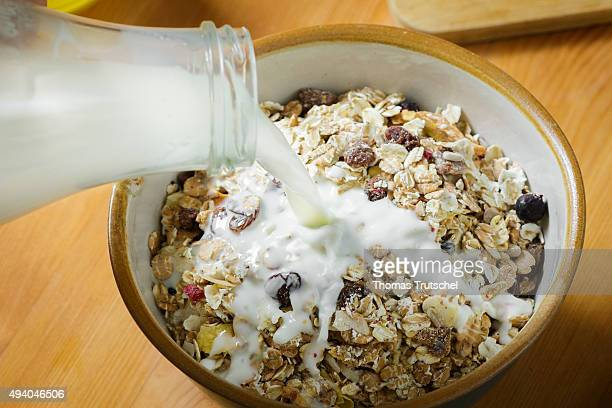 Muesli in a bowl is doused with milk from a bottle on October 24 2015 in Berlin Germany