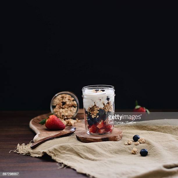 Muesli In Jar On Table Against Black Background