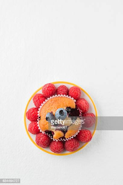 Muffin with blueberries and raspberries on plate