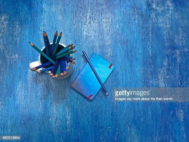 Mug full of blue pencils, blue note pad over a blue board. Still life.