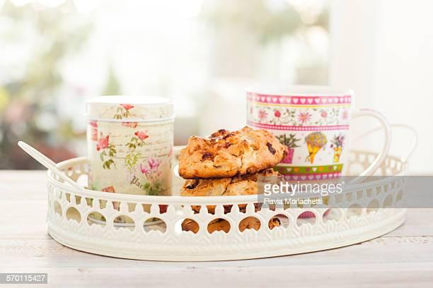 Mug, homemade cookies and tin on a tray