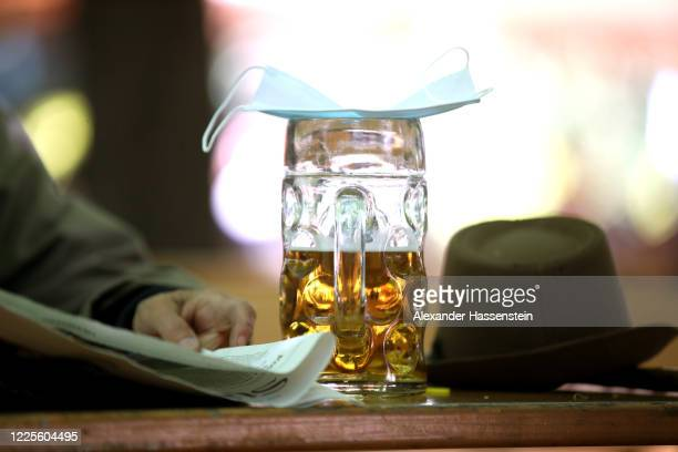 Mug of beer is covered with a protective face mask at the beer garden of the Hofbräukeller park on the first day beer gardens were allowed to reopen...