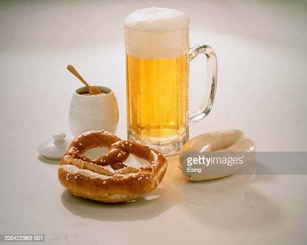 A mug of beer with a pretzel, white sausages and a jar of mustard