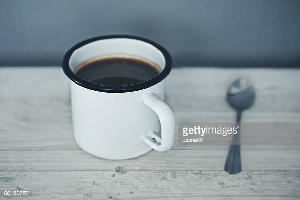 Mug of coffee and a spoon on a table