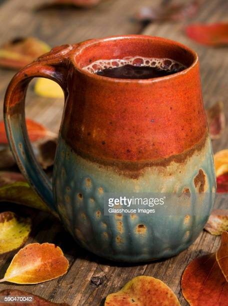 Mug of Coffee on Picnic Table With Autumn Leaves