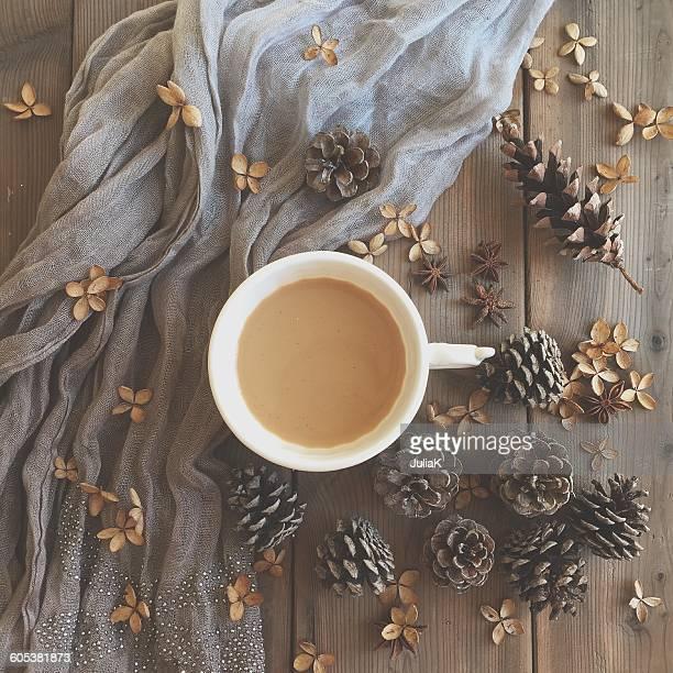 Mug of coffee, scarf, hydrangea petals and pine cones