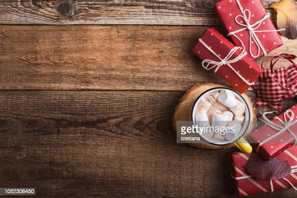 Mug of hot chocolate and Christmas gift boxes