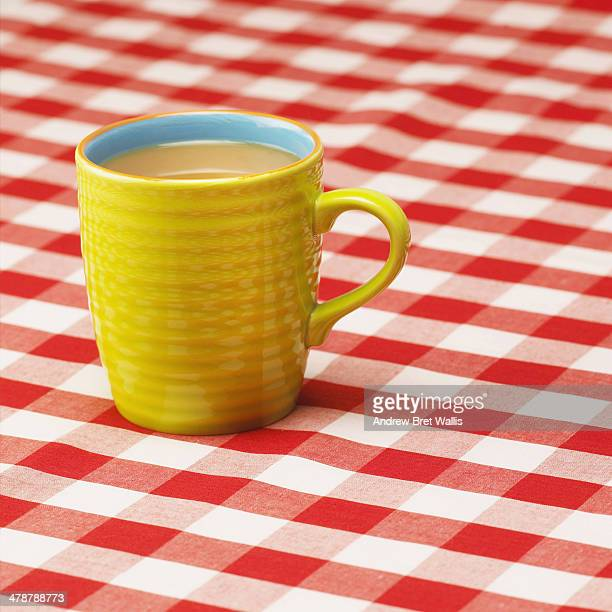 Mug of tea on a red chequered cafe' table cloth