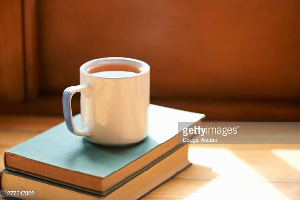 mug of tea on books. - book stock pictures, royalty-free photos & images