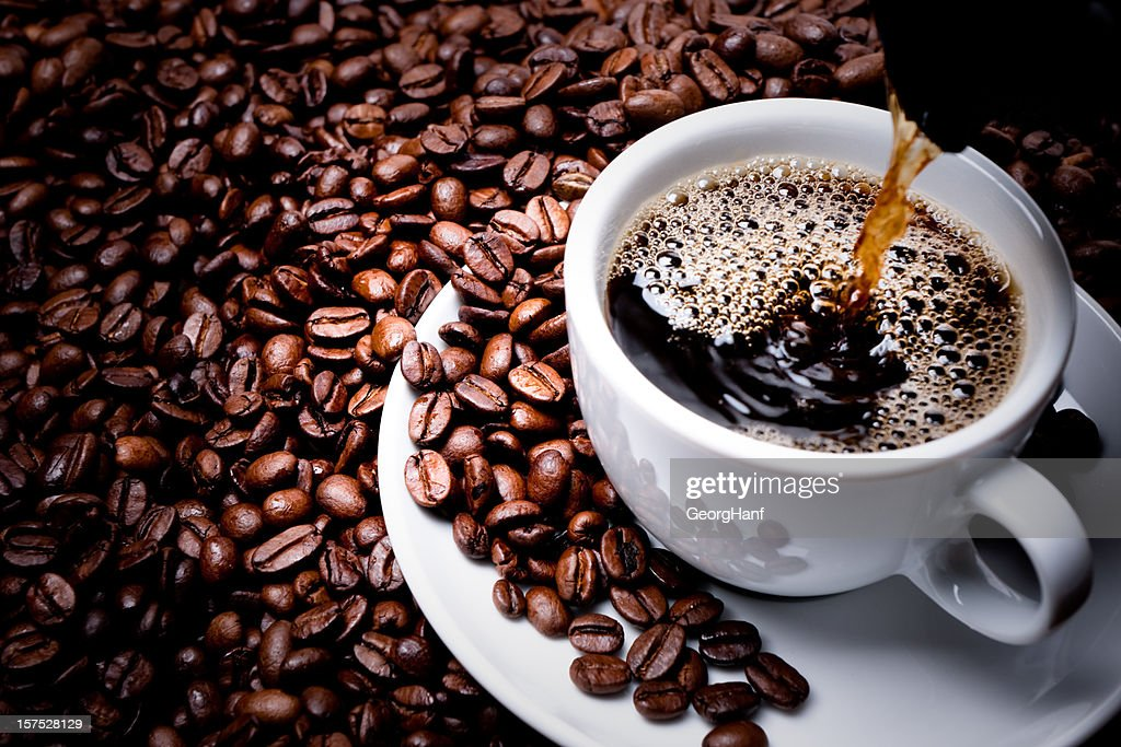 Mug on plate filled with coffee surrounded by coffee beans  : Stock Photo