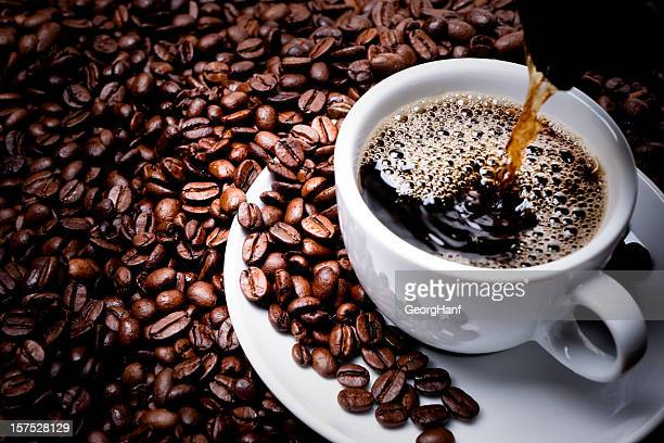 Mug on plate filled with coffee surrounded by coffee beans