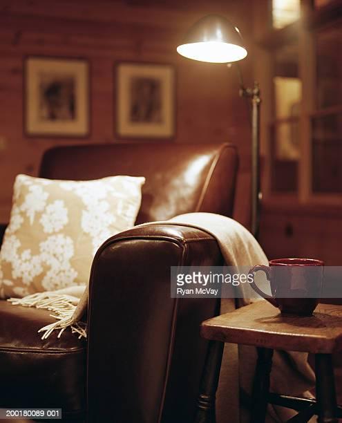 Mug on table beside armchair