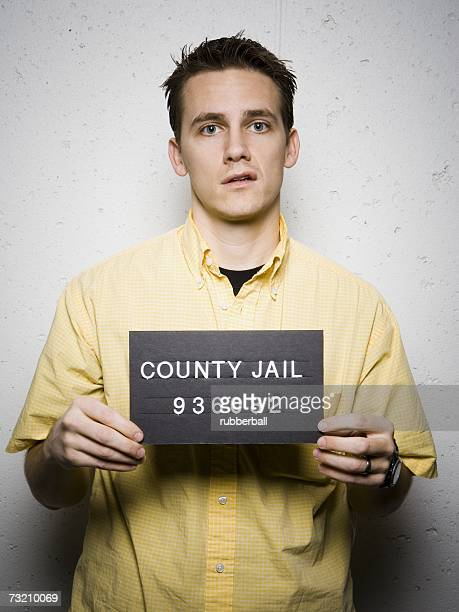Mug shot of casually dressed man sneering
