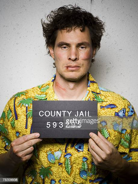 Mug shot of man in Hawaiian shirt with cuts and scrapes