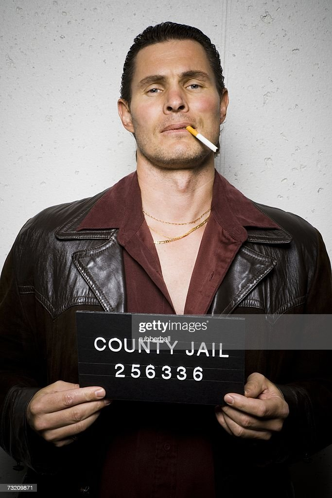 Mug shot of man with cigarette and gold chains : Stock Photo