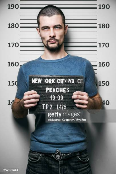 mug shot of young man holding placard against wall with measurement at police station - criminal stock pictures, royalty-free photos & images