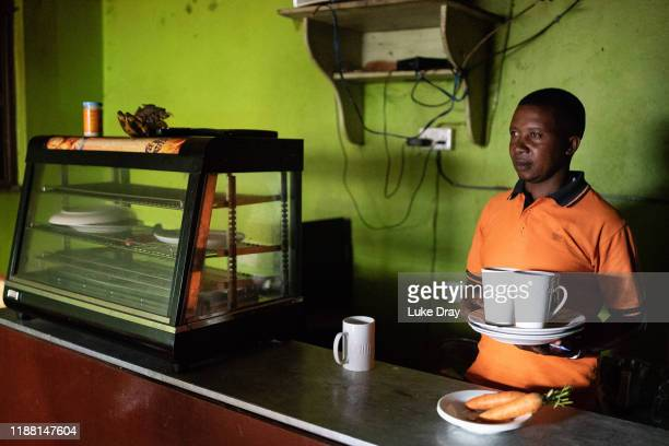 Mugarura Ronald , a Ugandan restaurant worker who has been working at the same restaurant for seven years, cleans inside his restaurant on November...