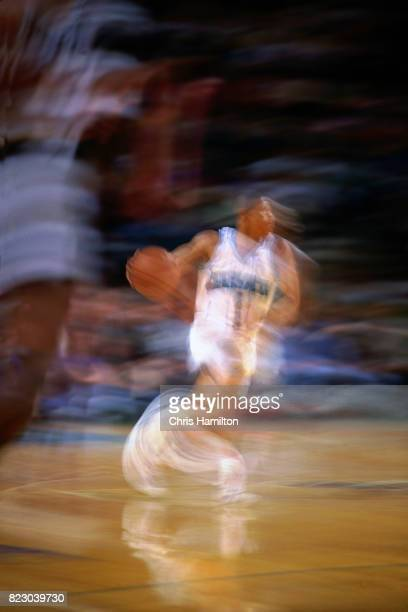 Muggsy Bogues of the Charlotte Hornets dribbles the ball up court against the Atlanta Hawks at the Omni Coliseum in Atlanta Georgia circa 1992 NOTE...
