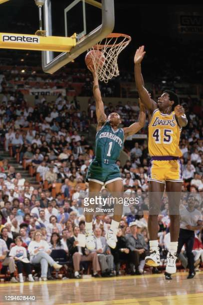 Muggsy Bogues, Point Guard for the Charlotte Hornets attempts a lay up shot to the basket over A.C. Green, Power Forward for the Los Angeles during...