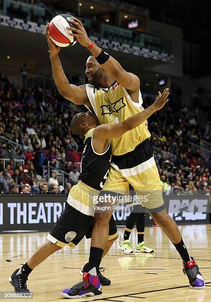 Muggsy Bogues'3'' of Team USA and Tracy McGrady of Team Canada battle for position during the NBA AllStar Celebrity Game at the Ricoh Coliseum on...