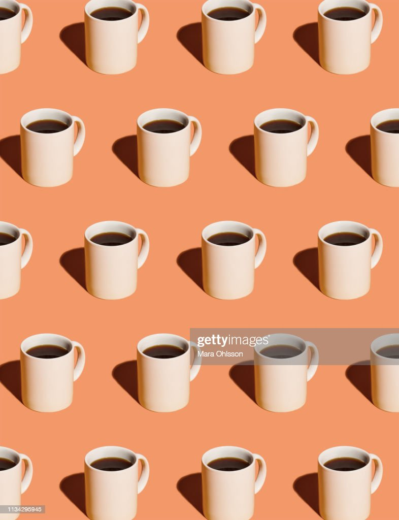 Mugs of black coffee in rows against peach background : Stock Photo