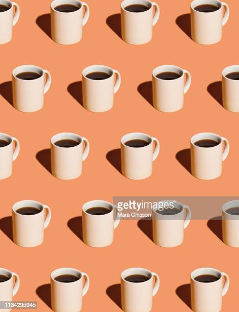 mugs of black coffee in rows against peach background - coffee stock pictures, royalty-free photos & images