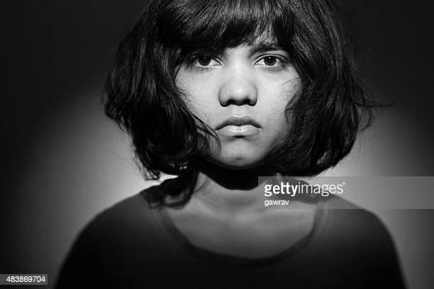 Mugshot of an unhappy angry teenage girl looking at camera.