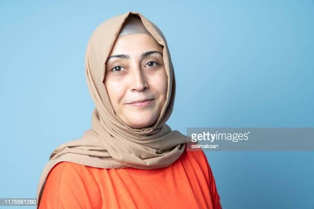 ヒジャーブとイスラム教徒の女性のマグショット - オレンジ色のシャツ ストックフォトと画像