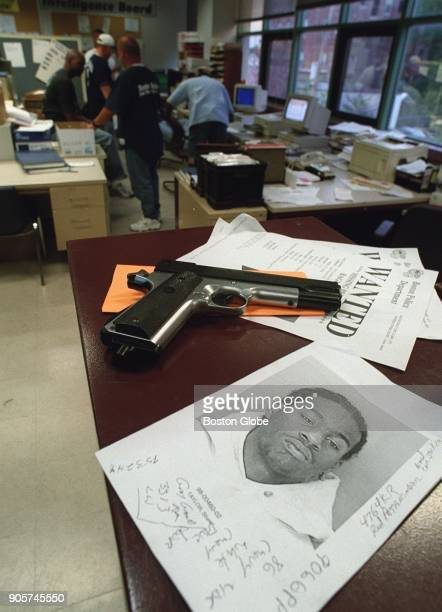 A mugshot of wanted suspect Sean Taylor rests next to a pellet gun seized from a recent arrestee at the office of the Boston Police Youth Violence...