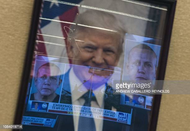 Mugshots of bombing suspect Cesar Sayoc are reflected on a portrait of US President Donald Trump prior to a press conference at the Department of...