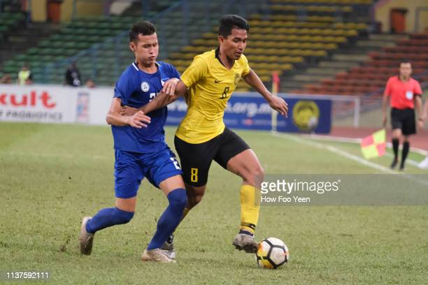 Muhamad Shahrul Nizam of Malaysia shields the ball from Jordan Jarvis of the Phillipines during the AFC U23 Championship qualifier between Malaysia...