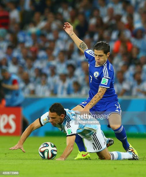 Muhamed Besic of Bosnia and Herzegovina challenges Maxi Rodriguez of Argentina during the 2014 FIFA World Cup Brazil Group F match between Argentina...
