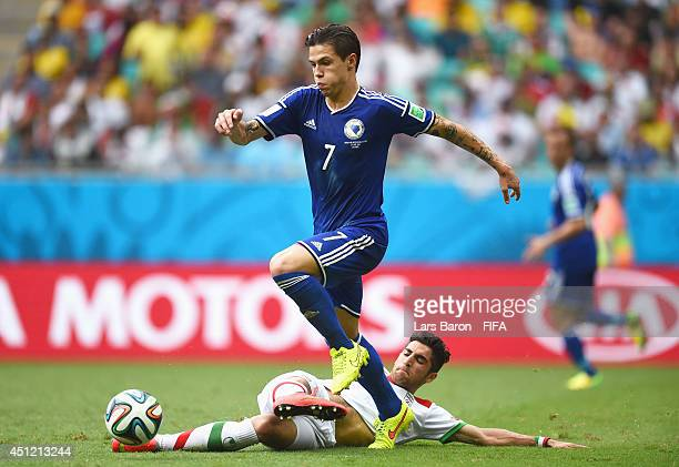 Muhamed Besic of Bosnia and Herzegovina is tackled by Alireza Jahan Bakhsh of Iran during the 2014 FIFA World Cup Brazil Group F match between...