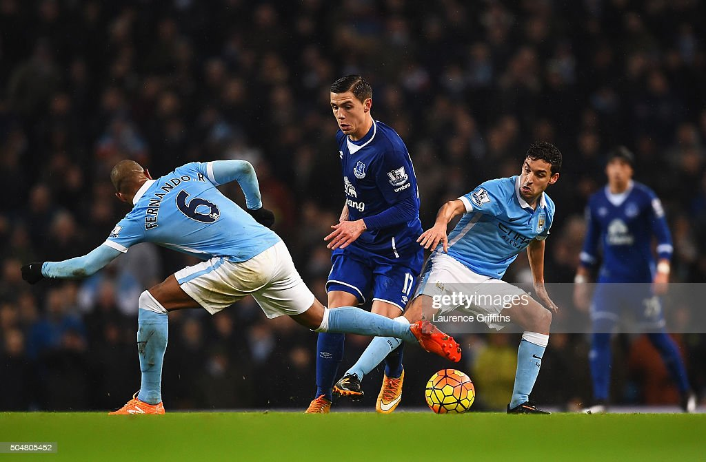 Muhamed Besic (C) of Everton competes for the ball against Fernando (L) and Jesus Navas (R) of Manchester City during the Barclays Premier League match between Manchester City and Everton at the Etihad Stadium on January 13, 2016 in Manchester, England.