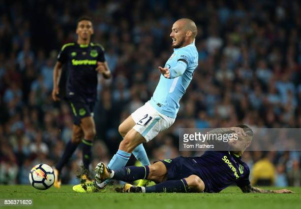 Muhamed Besic of Everton tackles David Silva of Manchester City during the Premier League match between Manchester City and Everton at Etihad Stadium...