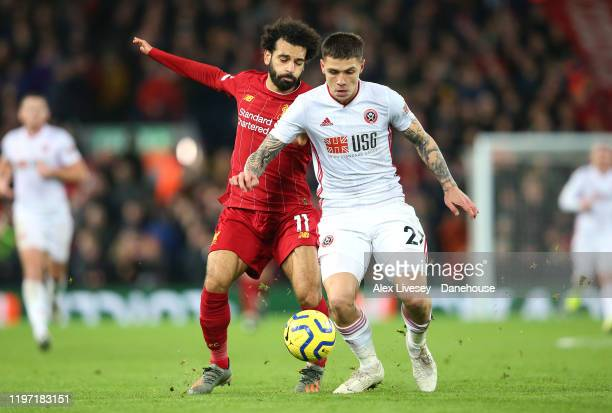 Muhamed Besic of Sheffield United holds off a challenge from Mohamed Salah of Liverpool during the Premier League match between Liverpool FC and...