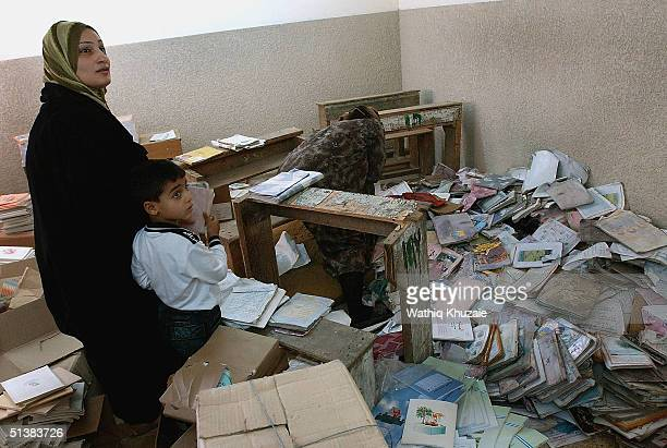 Muhammad Abdulrazaq age 6 stands with his mother to receive text books as a teacher searches for decent copies from a pile of old school books at the...
