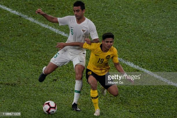 Muhammad Akhyar Rashid of Malaysia clashes with Otavio Dutra of Indonesia during the 2022 Qatar FIFA World Cup Asian qualifier group G match between...