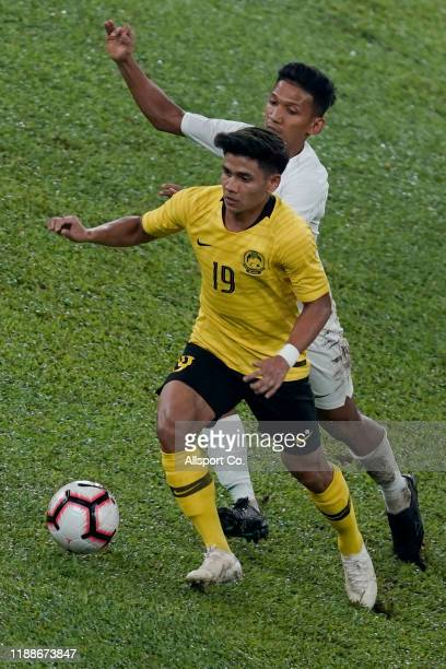 Muhammad Akhyar Rashid of Malaysia is tackled by Teuku Muhd Ichsan of Indonesia during the 2022 Qatar FIFA World Cup Asian qualifier group G match...