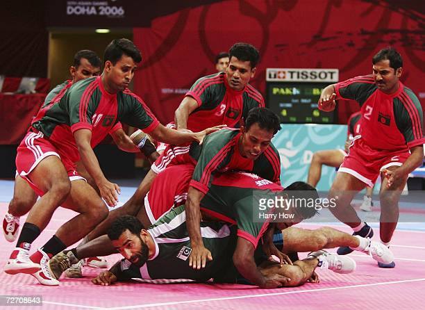 Muhammad Akram of Pakistan is held down by Bangladesh players during the Men's Kabaddi Round Robin Match Five between India and Bangladesh at the...